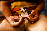 Namwan, a 63-year-old ladyboy in Phrae, Thailand, holds up an old picture of herself in women's clothes, as a young boy.