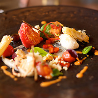 Lunch starter dish (90ZAR) of homedried tomato, sesame and aubergine puree, burnt aubergine jelly, goats cheese mousse. Dish at Chef Luke Dale-Roberts' acclaimed restaurant The Test Kitchen. The restaurant is located inside the Old Biscuit Mill in Cape Town's Woodstock neighborhood.
