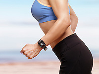 Woman jogging outdoors at the beach with Apple Watch smartwatch on her wrist displaying daily activity and exercise