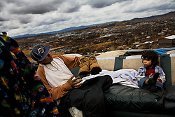 A young boy sits on a couch with a neighbor  in the hills of Nogales. He and his family have been sleeping outside since their tin and cardboard shack burned to the ground two weeks before. Even before the accident the family had no water or electricity and their only source of income was selling scavenged trash.