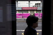 Man at bus stop outside London Metropolitan University's Holloway Road buildings.