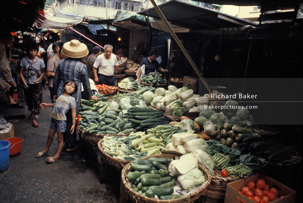 A child leans against an adult shopping for fresh vegetables at an Aberdeen street market, on 16th April 1979, in Hong Kong, (while still UK).