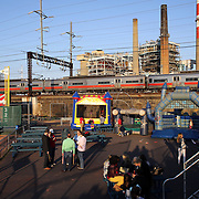 The Bridgeport Harbor Power Station provides a back drop to the ballpark in the late evening light as children play on bouncing castles as the Bridgeport pitching staff warm up for the game before the Bridgeport Bluefish V Southern Maryland Blue Crabs, Atlantic League, Minor League ballgame at Harbor Yard Ballpark, Bridgeport, Connecticut, USA. Photo Tim Clayton