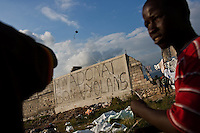 """A boy flies a homemade kite in the Pechinat camp in Jacmel. The writing on the wall reads, """"A God without violence."""" January's earthquake killed hundreds of thousands of people and caused significant and lasting structural and economic damage in the Caribbean nation."""