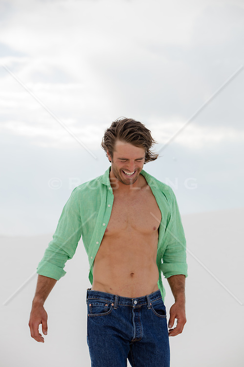 man with an open shirt laughing outdoors
