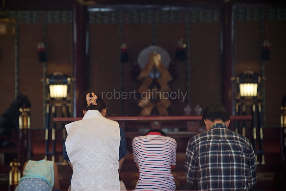 People pray inside Fujisan Hongu Sengen Taisha in Fujinomiya City, Shizuoka Prefecture Japan on 01 Oct. 2012.  Photographer: Robert Gilhooly