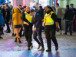 © Licensed to London News Pictures . 01/01/2018. Manchester, UK. Security assist a staggering outside the Printworks . Revellers celebrate the start of the New Year in Manchester City Centre . Photo credit: Joel Goodman/LNP