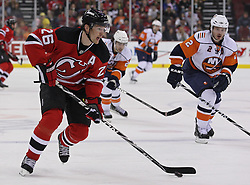 Apr 10, 2010; Newark, NJ, USA; New Jersey Devils left wing Patrik Elias (26) skates with the puck while being chased by New York Islanders defenseman Mark Streit (2) during the first period at the Prudential Center.