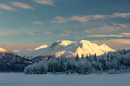 Late afternoon sun illuminates the snow covered Chugach Mountains along the Knik River in Southcentral Alaska. Winter.