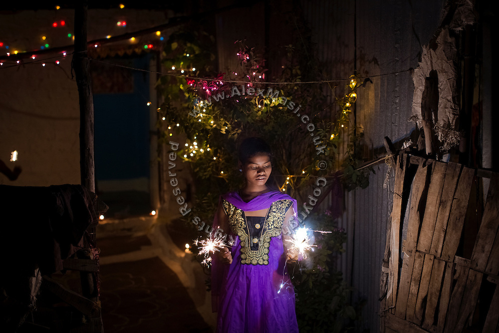 Poonam, 12, is celebrating Diwali, the Hindu festival of lights, in the courtyard of her family's newly built home in Oriya Basti, one of the water-contaminated colonies in Bhopal, central India, near the abandoned Union Carbide (now DOW Chemical) industrial complex, site of the infamous '1984 Gas Disaster'.
