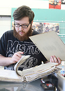 Austin DeCourley goes through a binder of names Wednesday, April 13, 2016 at Pegasus Records in Florence, Ala. to see who owns the vinyl in his hand. One of the tasks to prepare for the store closing is that DeCourley and other employees go through all the items in storage.