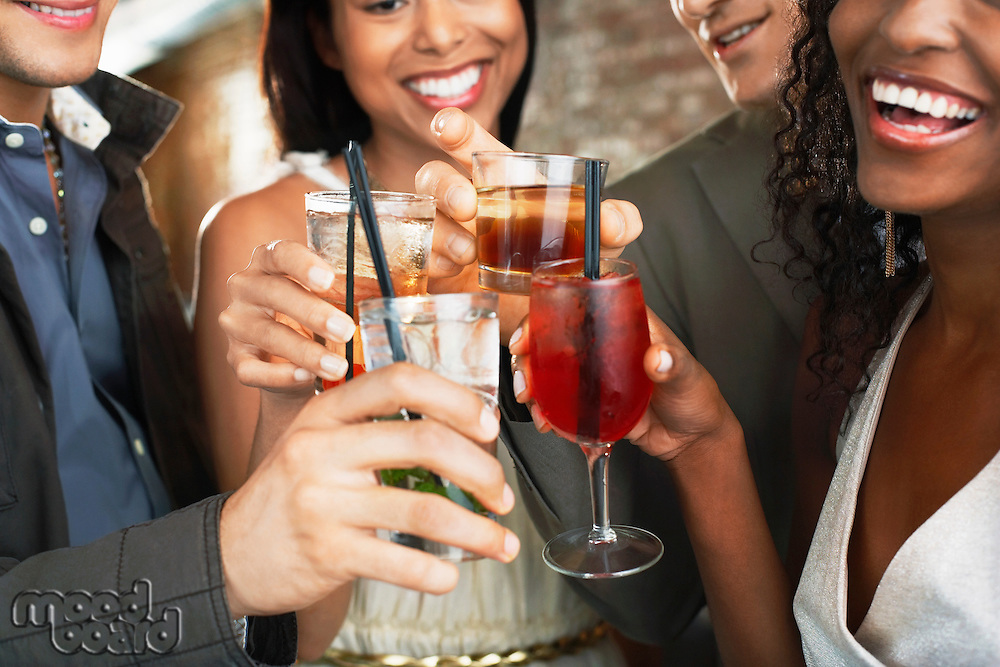 Friends toasting  in bar close up on glasses