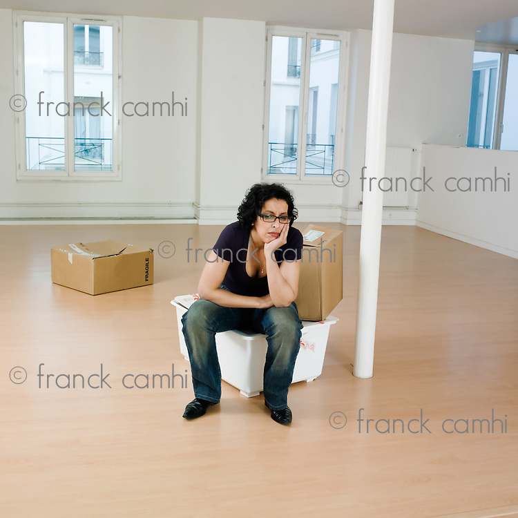 man sitting on the floor inside an empty loft appartement