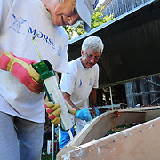 "August 23, 2008 -- BATH, Maine. Carole, left, and Paul Johnson of Bath apply wood glue to the lower edge of their new boat at Maine Maritime Museum's (MMM) boatbuilding workshop in Bath on Saturday afternoon. ""My plan is that when my grandchildren come by that this will be their boat,"" said Carole of her first boat.  .Kurt Spiridakis, Boat Shop Manager oversaw the MMM's first ever boat building workshop this weekend by helping the Johnsons and a family from Gorham build two flat bottomed Bevin Skiffs. The design comes from Joe Youcha, associated with the Alexandria Seaport Foundation in Virginia and the final products, launched Sunday afternoon, weighs about 90 lbs., fully rigged.  Photo by Roger S. Duncan."