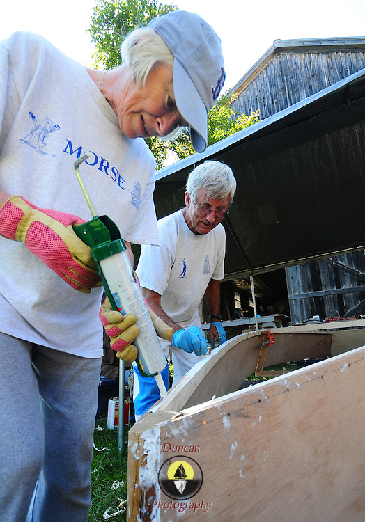 """August 23, 2008 -- BATH, Maine. Carole, left, and Paul Johnson of Bath apply wood glue to the lower edge of their new boat at Maine Maritime Museum's (MMM) boatbuilding workshop in Bath on Saturday afternoon. """"My plan is that when my grandchildren come by that this will be their boat,"""" said Carole of her first boat.  .Kurt Spiridakis, Boat Shop Manager oversaw the MMM's first ever boat building workshop this weekend by helping the Johnsons and a family from Gorham build two flat bottomed Bevin Skiffs. The design comes from Joe Youcha, associated with the Alexandria Seaport Foundation in Virginia and the final products, launched Sunday afternoon, weighs about 90 lbs., fully rigged.  Photo by Roger S. Duncan."""