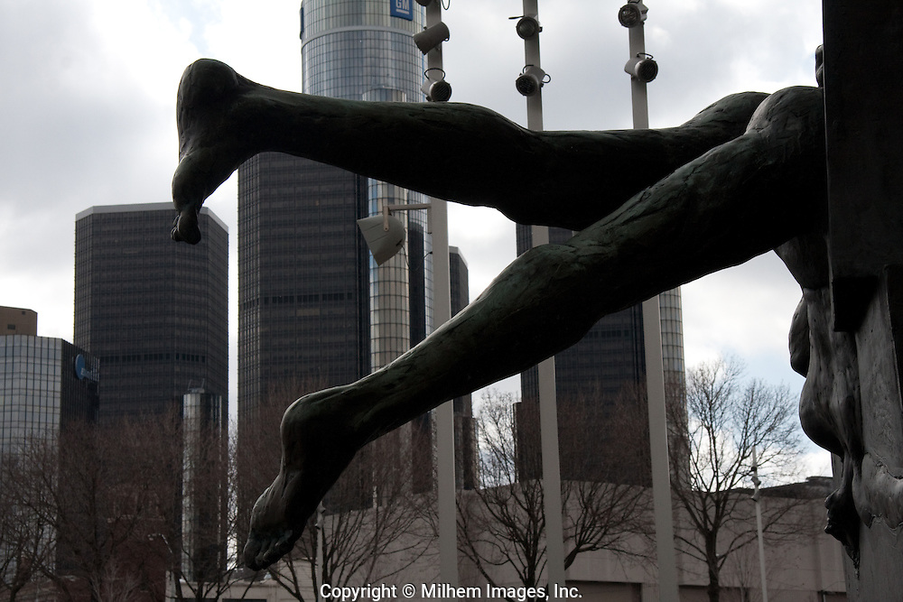 Detroit Renissance Center photographed behind a sculpture of two tangling legs.