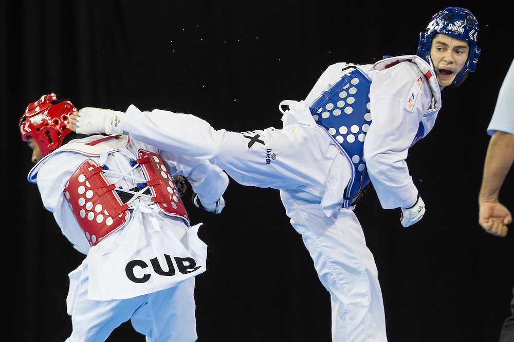 Rene Lizarraga (R) of the Mexico kicks Jose Cobas of Cuba during their semi-final contest in men's taekwondo -80 kg division at the 2015 Pan American Games in Toronto, Canada, July 21,  2015.  AFP PHOTO/GEOFF ROBINS