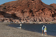 Ship passengers explore beach and sandstone cliffs of Puerto Gato, Baja, Mexico.