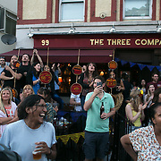A pub crowd cheers the last steel band float of the day passing by. Hackney carnival 2016 took place on a hot Indian sumers day, September 2016 with the streets full of partying people.
