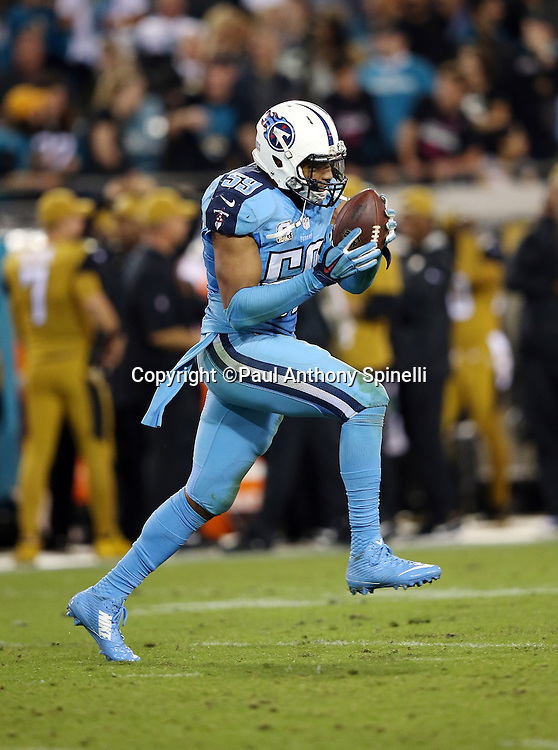 Tennessee Titans inside linebacker Wesley Woodyard (59) runs with the ball as he celebrates after a fourth quarter interception during the 2015 week 11 regular season NFL football game against the Jacksonville Jaguars on Thursday, Nov. 19, 2015 in Jacksonville, Fla. The Jaguars won the game 19-13. (©Paul Anthony Spinelli)