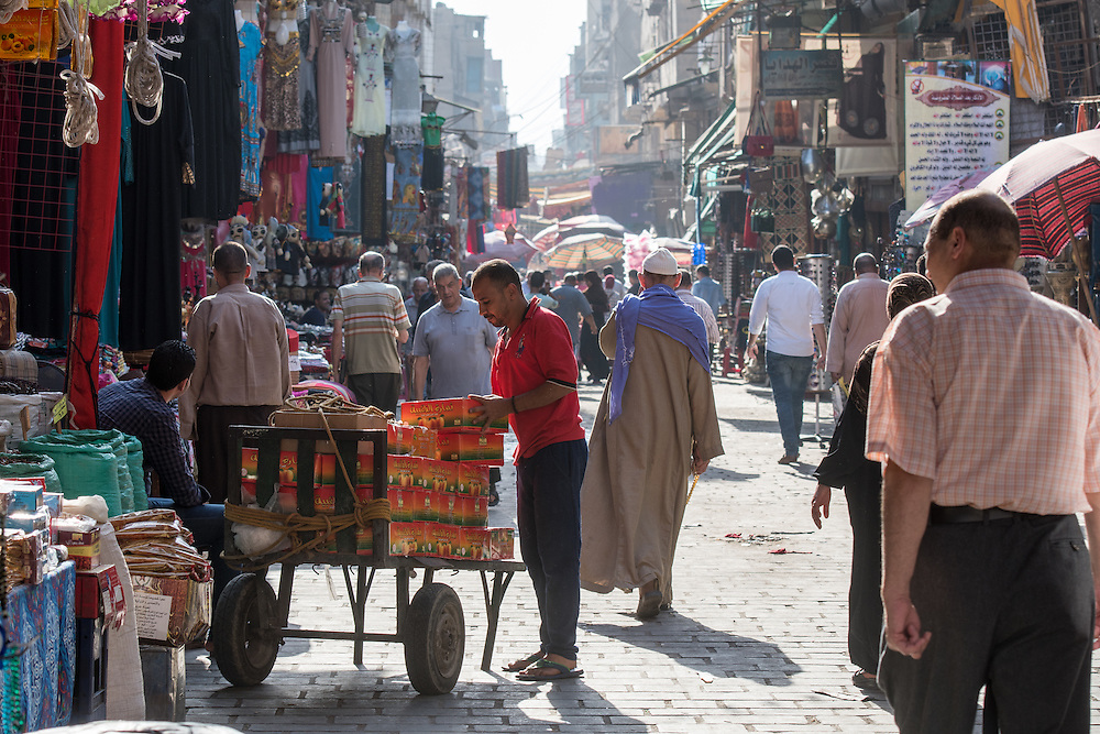 Cairo, Egypt. Egyptian men and covered women in headscarves walking through shops and speaking to shop owners along an alleyway in the outdoor bazaar/ flea market Khan el-Khalili in Cairo.