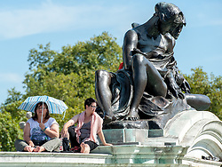 © Licensed to London News Pictures. 22/08/2015. London, UK. A woman sitting on the Queen Victoria Memorial uses a umbrella to shade from the sun. Photo credit: Pete Maclaine/LNP