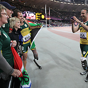 LONDON 2012 PARALYMPIC GAMES..Pic shows Oscar Pistorius  celebrating with his team mates and taking a photo of them with friends in the crowd after winning gold on Wednesday evening in the 100m relay at the Paralympics Games in London September 9th 2012... Oscar Pistorius gained revenge for his shock 200 metres defeat by holding off his Brazilian conqueror on the final leg of the 4x100m relay to claim a belated first gold medal of London 2012..The 25-year-old brought the South African team home in a new world record of 41.78 seconds to crown a night which saw the great blade debate take another twist..Pistorius was pitted in direct opposition with Alan Fonteles Oliveira and American Blake Leeper, both of whose long blades he had fiercely criticised in the wake of his shock loss on Sunday. But he held off the Brazilian strongly down the home straight to roars from the crowd..Brazilian and American disappointment was compounded when both teams, who had come home second and third respectively, were disqualified.