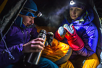 A female mountaineer pours warm tea into a mug for her fellow on a cold winter night in Mont Blanc Massif.