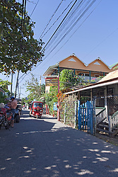 A red tuk-tuk makes its way down the potholed main street of Utila town.