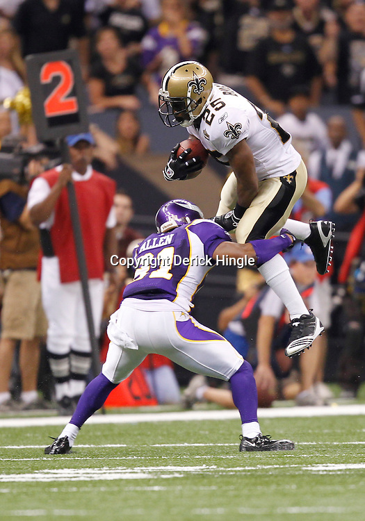 September 9, 2010; New Orleans, LA, USA;  New Orleans Saints running back Reggie Bush (25) leaps over Minnesota Vikings cornerback Chris Cook (31)during first half of the NFL Kickoff season opener at the Louisiana Superdome. Mandatory Credit: Derick E. Hingle