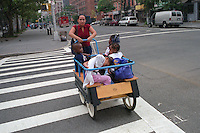 Woman taking a group of small children to the park in a cart in Manhattan NYC.