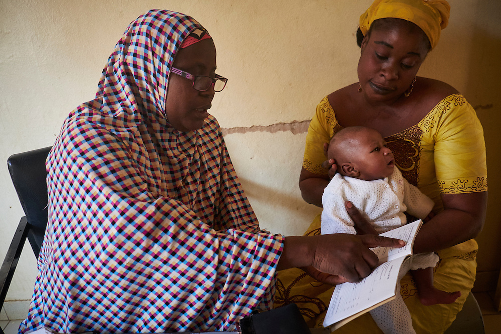 Nurse Amadou Aissatou talks with mother Zoubeirou Mariana, 33 years old after administering vaccinations to baby Mohamed, 3 weeks old at the Banga Bana health centre, Niamey, Niger on February 16, 2016.
