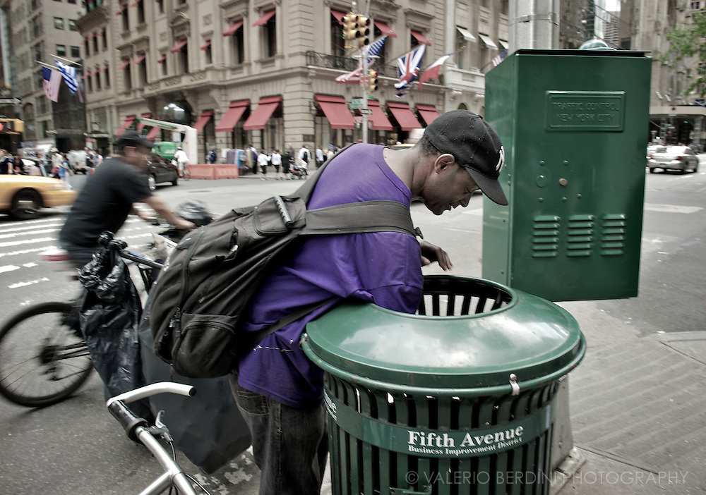 A homeless man looking for recyclable material in a bin of the Fifth Avenue.