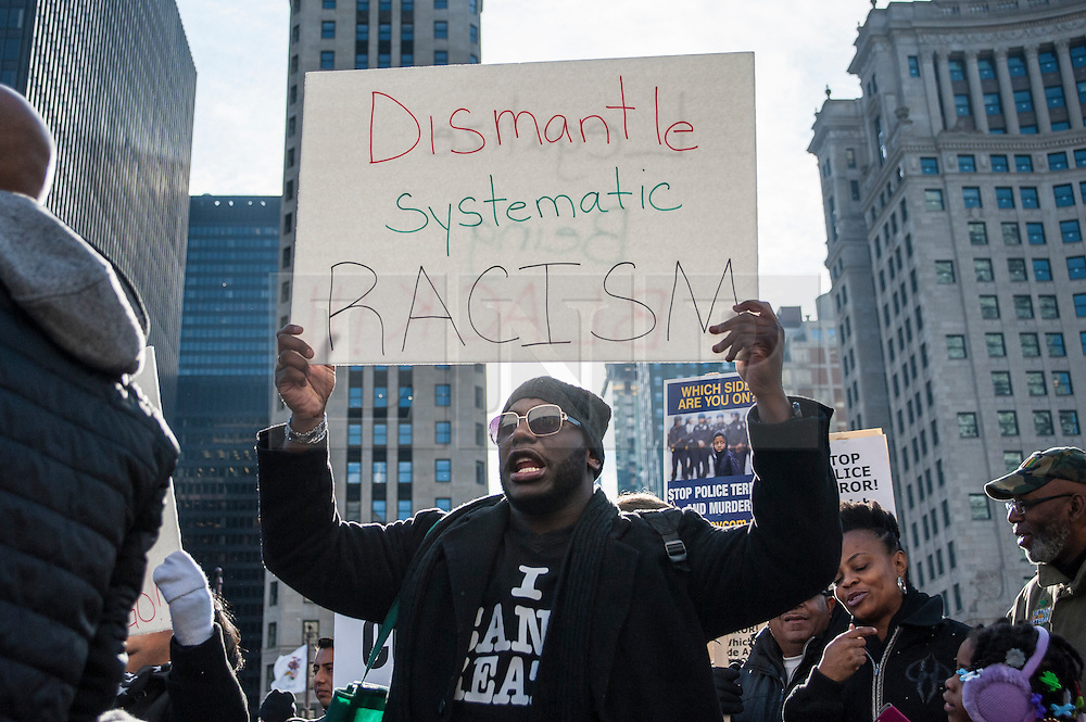 """© Licensed to London News Pictures. 24/12/2015. Chicago, USA. Hundreds of people gather to march down Michigan Avenue's """"Magnificent Mile"""" shopping district on Christmas Eve to protest against the alleged police cover up related to the fatal shooting of Laquand McDonald by a Chicago policeman.  Flanked by members of the Chicago police force, protestors were chanting """"16 shots and a cover up,"""" and calling for Chicago Mayor Rahm Emanuel to resign, on what was described as """"Black Christmas"""".  Photo credit : Stephen Chung/LNP"""