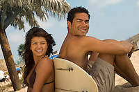Cute Surfer Couple Sitting on Beach