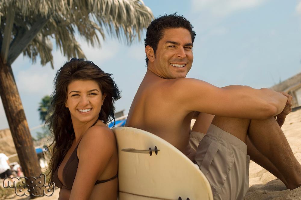 Cute Surfer Couple Sitting on Beach