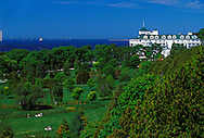 THE GRAND HOTEL OVERLOOKING A GOLF COURSE ON MACKINAC ISLAND, MICHIGAN WITH THE MACKINAC BRIDGE IN BACKGROUND.