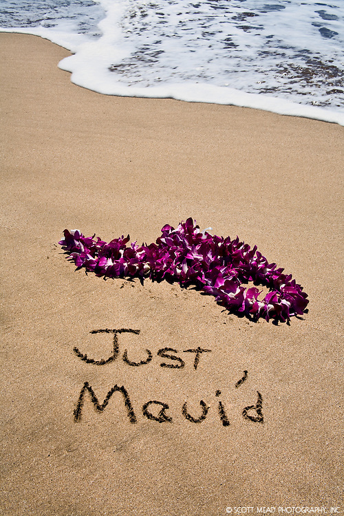 Just Mauid written in sand of beach on Maui, Hawaii, flower leis
