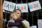 A father and daughter hug each other outside Carnegie Library in Herne Hill, south London while occupiers remain inside the premises on day 6 of its occupation, 5th April 2016. The angry local community in the south London borough have occupied their important resource for learning and social hub for the weekend. After a long campaign by locals, Lambeth have gone ahead and closed the library's doors for the last time because they say, cuts to their budget mean millions must be saved.