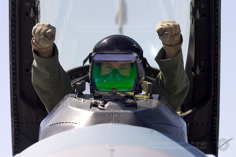 "Eyes peering through his Head's Up Display (HUD), Major Derek ""Tazz"" Routt gives the ""All Clear"" signal prior to taxiing. The F-16's advanced Head's Up Display allows the pilot to acquire the aircraft's most important flight characteristic information at a glance rather than looking down into the cockpit losing sight of forward view. As callsign 'MiG-6', ""Tazz"" will join up with five other F-16C's from the 64th Aggressor Squadron as they engage the Blue Team over the Nellis Range Complex."
