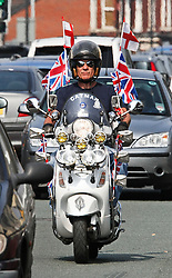 © licensed to London News Pictures. UK  23/04/2011. Kevin Sibley riding his scooter through Stockport today (23/04/2011) covered in union flags and St George's crosses to celebrate St George's day. See special instructions for rates. Photo credit should read Andy Barnes/LNP