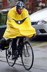 © Licensed to London News Pictures. 30/01/2014<br /> Wet and cold weather conditions continue across the UK. <br /> Rainy weather this afternoon (30.01.2014)  this cyclist wears his yellow waterproof jacket as in rides his bike along St Mary Cray,High Street,Orpington,Kent.<br /> Photo credit :Grant Falvey/LNP