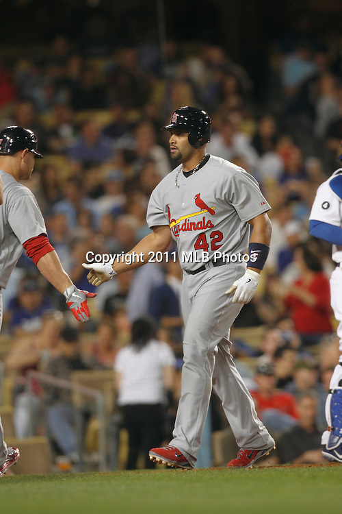 LOS ANGELES, CA - APRIL 15:  Albert Pujols #5 of the St. Louis Cardinals gets congratulations from a teammate after hitting a two run home run that gives the Cardinals a 6-2 lead in the top of the fifth inning during the game between the St. Louis Cardinals and the Los Angeles Dodgers on Friday April 15, 2011 at Dodger Stadium in Los Angeles, California. (Photo by Paul Spinelli/MLB Photos via Getty Images) *** Local Caption *** Albert Pujols