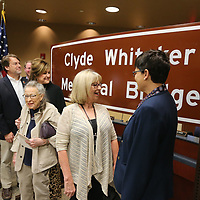Deborah Whitaker George of Hernando, center, and Beth Whitaker, right, join other family members to unveil the sign to dedicate the bridge on Coley Road that spans I-22 the Clyde Whitaker Memorial Bridge.