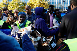 October 31, 2016 - Paris, France - Migrants carry their belongings at a makeshift camp at the Stalingrad metro stations during a police operation aiming at a future evacuation of the camp. Seen ADRA Human fundation stop by and gave them some food in Paris on October 31, 2016. (Credit Image: © Mehdi Taamallah/NurPhoto via ZUMA Press)