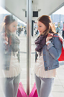 Young woman in casuals window shopping
