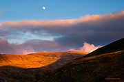 I was in the shadows of Foel Goch and Moel Cynghorion, with the sun setting behind me. I had put my camera away for the day but suddenly the clouds cleared to reveal a beautiful scene. <br /> <br /> I scrabbled in the rucksack to fetch the Fuji before the scene changed. I balanced my camera on a dry-stone wall to capture the near-full moon in a deep blue sky, high above the rolling foothills of Snowdon that were still bathed in warm sunshine.