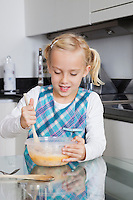 Girl making cookies in mixing bowl at kitchen