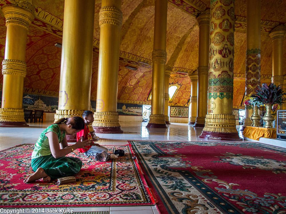 10 NOVEMBER 2014 - SITTWE, MYANMAR:  A girl prays in Lokananda Paya, the main Buddhist pagoda (paya) in Sittwe, Myanmar. The pagoda was dedicated in 1997. Sittwe is a small town in the Myanmar state of Rakhine, on the Bay of Bengal.   PHOTO BY JACK KURTZ