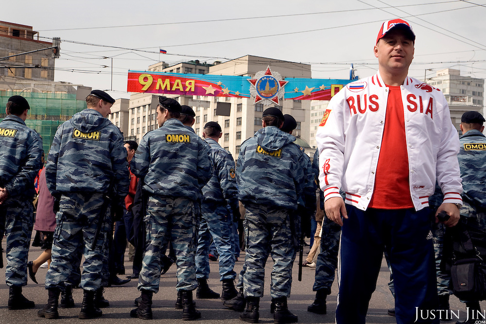 "A man in ""Russia"" jacket stands in front of riot police guarding a demonstration by Communist supporters on Labour Day."